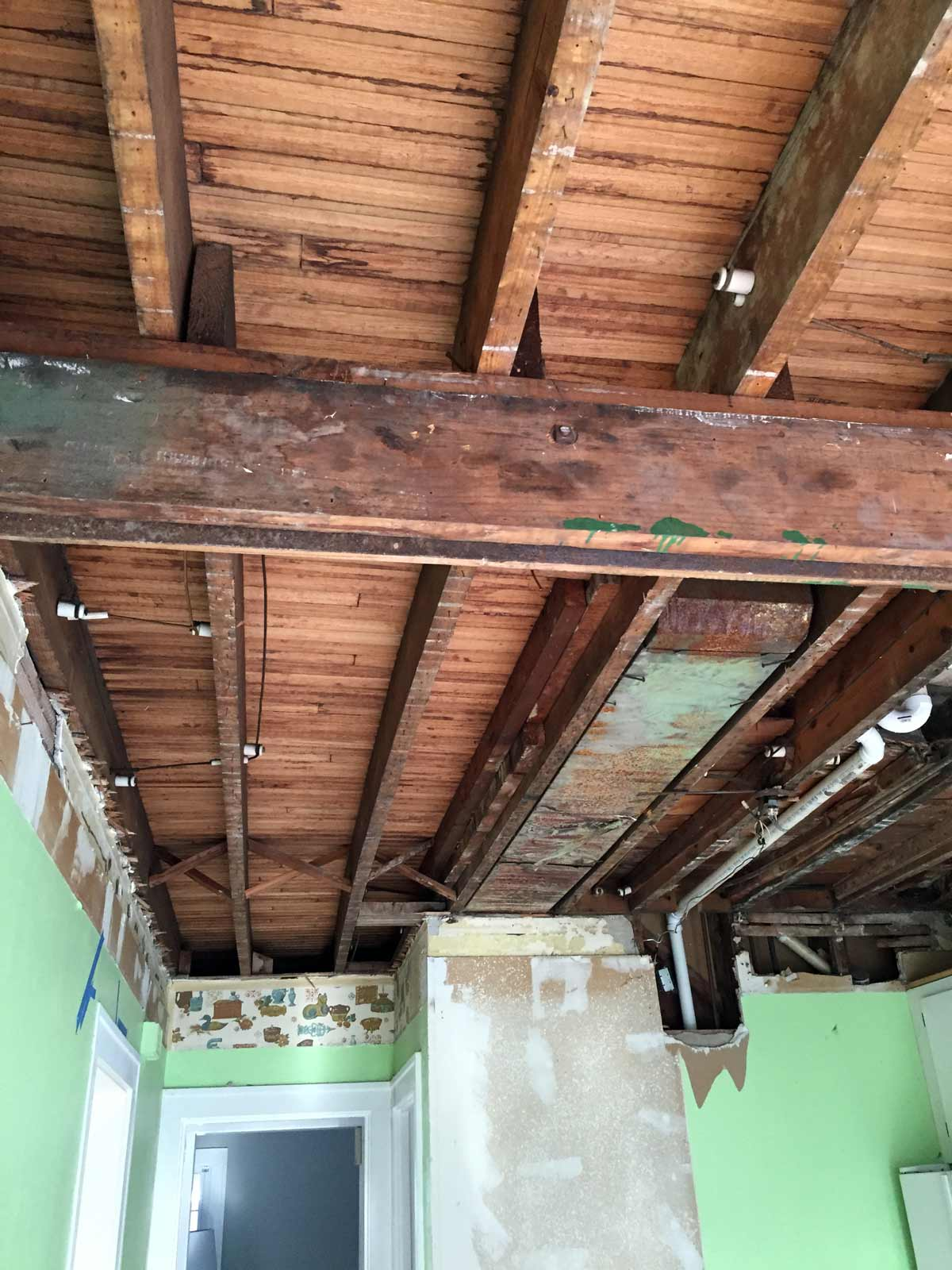 Exposed beams after removing drywall, plaster, and lath ceilings under drop ceiling