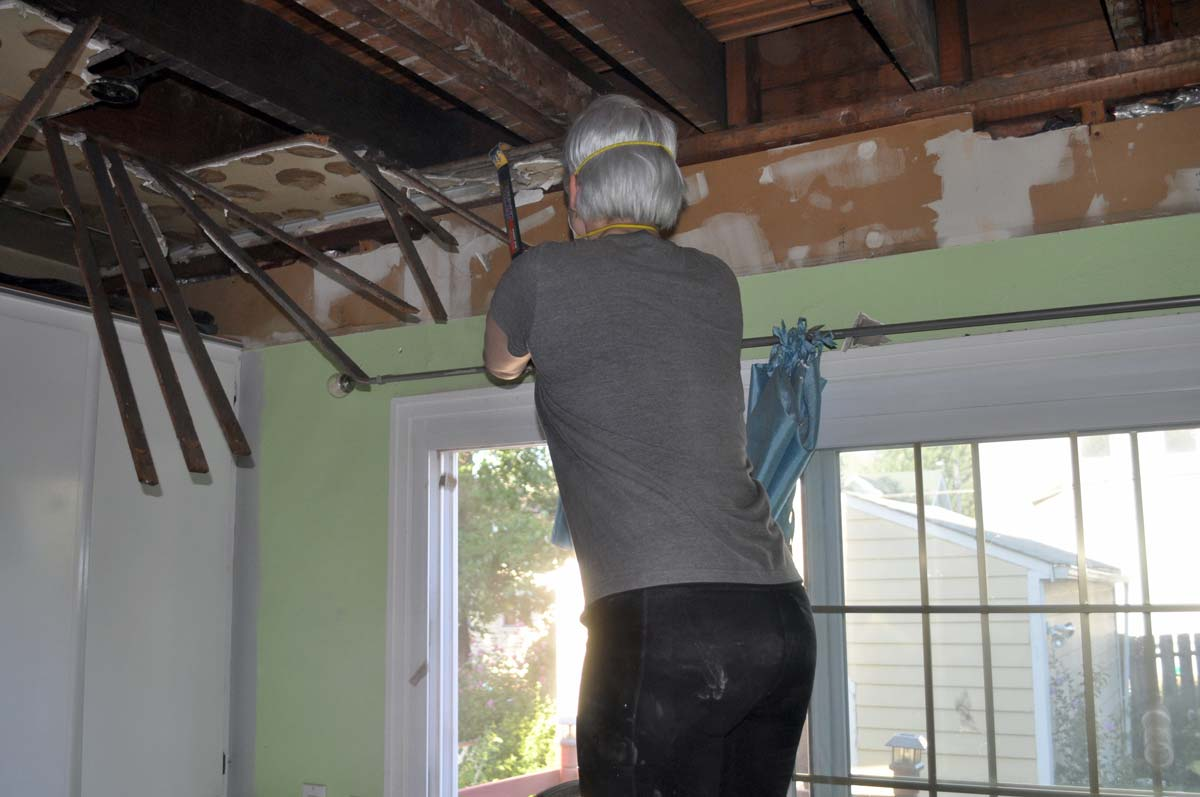 Using a crowbar for removing drywall, plaster, and lath ceilings under a drop ceiling
