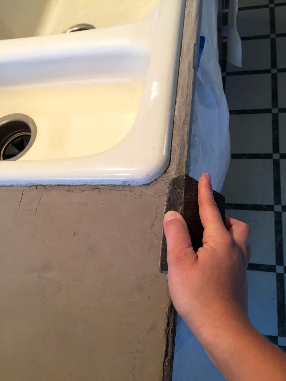 hand sanding the front edge of my DIY feather finish concrete over tile counters